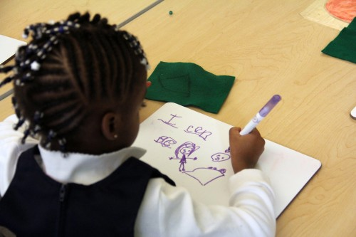 A pre-K student works on a writing assignment in a DC classroom